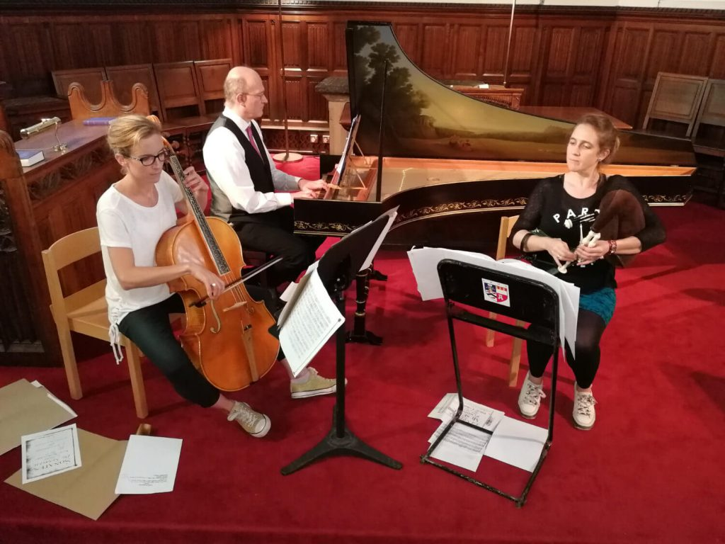 Three musicians rehearsing on baroque cello, musette and harpsichord
